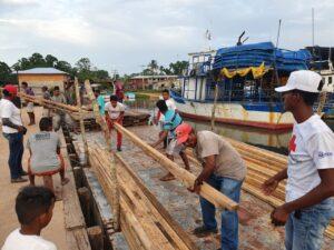 Comunitarios contribuyen en la descarga de los materiales de construcción que les serán entregados